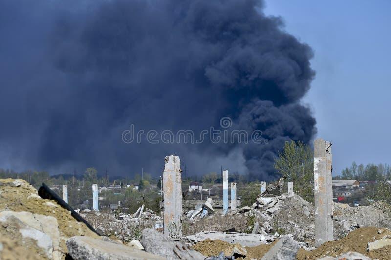 Stos betonowy gruz z sterczącym rebar na tle gęsty czerń dym w niebieskim niebie fotografia stock