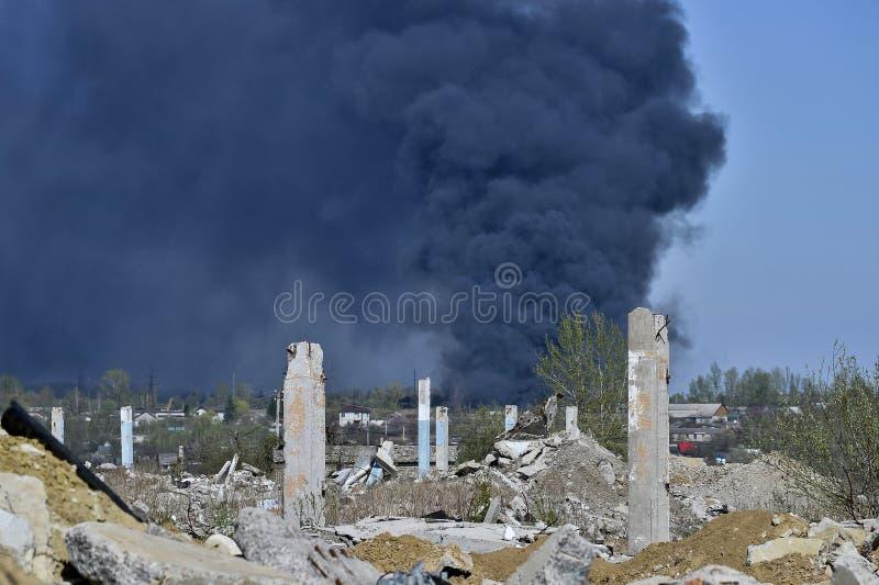 Stos betonowy gruz z sterczącym rebar na tle gęsty czerń dym w niebieskim niebie zdjęcia stock