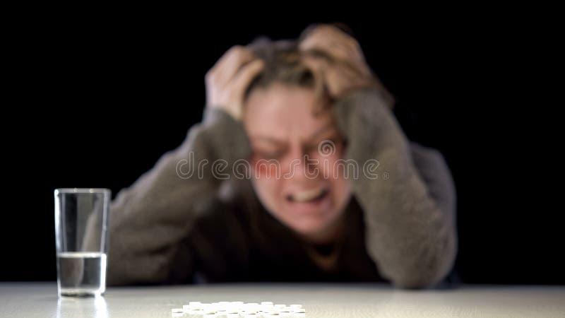 Stos białe pigułki i wodnego szkła stół, beznadziejny przemocy ofiary tło zdjęcie stock