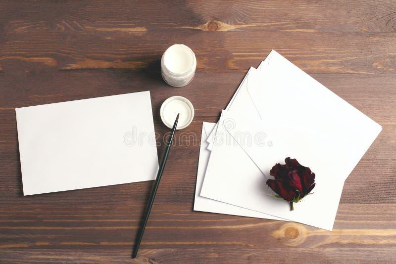 Stos białych kopert na drewnianym ciemnym tle i pędzel z białą farbą, układ twórczy, płaska warstwa obrazy stock