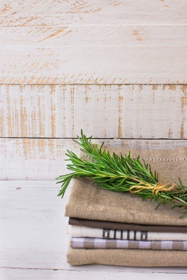 Stos brogujący fałdowi kuchenni ręczniki na białej deski drewnianym tle, rozmaryn kapuje, nieociosany minimalistic styl zdjęcia stock