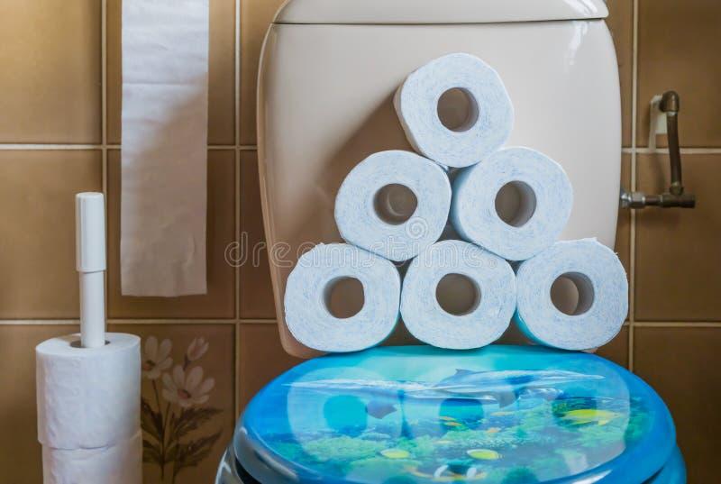 Stos brogujący papier toaletowy na wodnej szafy siedzeniu, wnętrze łazienka, sanitarny tło fotografia royalty free