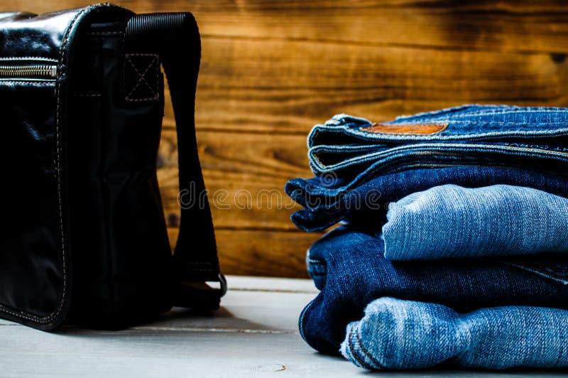 Stos cajgi i torba na drewnianym tle fotografia stock