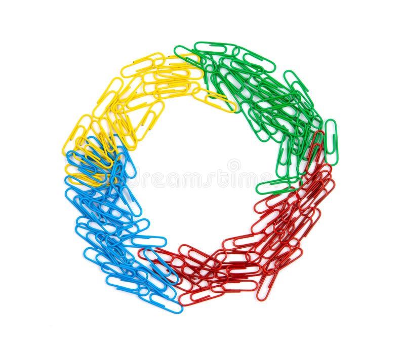Stos czerwień, zieleń, błękit i żółci papierowych klamerek kłamstwa w centrum prześcieradło w round pierścionku, kształtujemy na  zdjęcie royalty free