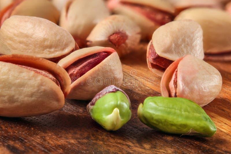 Stos czerwone Tureckie pistacje na drewnianej desce Dwa one strugali, zielona dokrętka widoczna zdjęcie stock