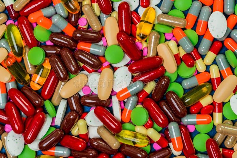 Stos kolorowe pastylki i kapsuł pigułki Pełna rama medycyna, witaminy i nadprogramy, Odgórny widok dużo pigułki tło obraz royalty free