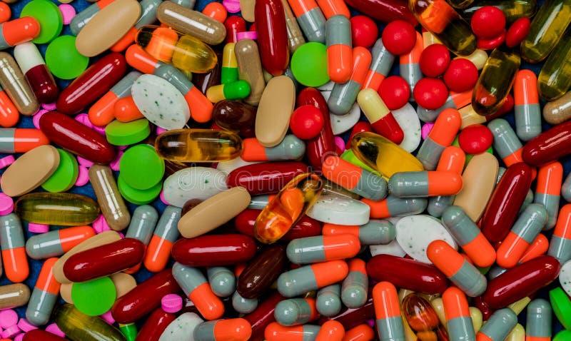 Stos kolorowe pastylki i kapsuł pigułki Pełna rama medycyna, witaminy i nadprogramy, Odgórny widok dużo pigułki tło obraz stock