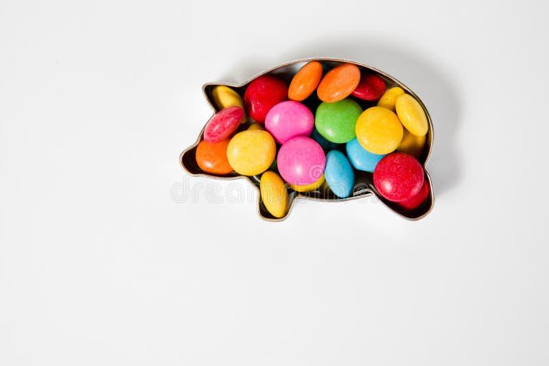 Stos kolorowi cukierków cukierki w kształcie świnia biały tło - wieprz - ilustracji
