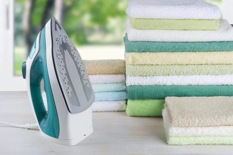 Stos kolorowi ręczniki i elektryczny żelazo, odprasowywa odzieżowego pojęcie obraz royalty free