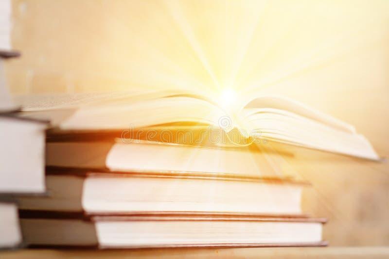 Stos książki z otwartą książką z promieniami światło Pojęcie obraz royalty free