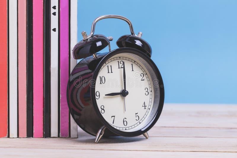 Stos magazyn książki z budzikiem na drewnianym z b i obraz royalty free
