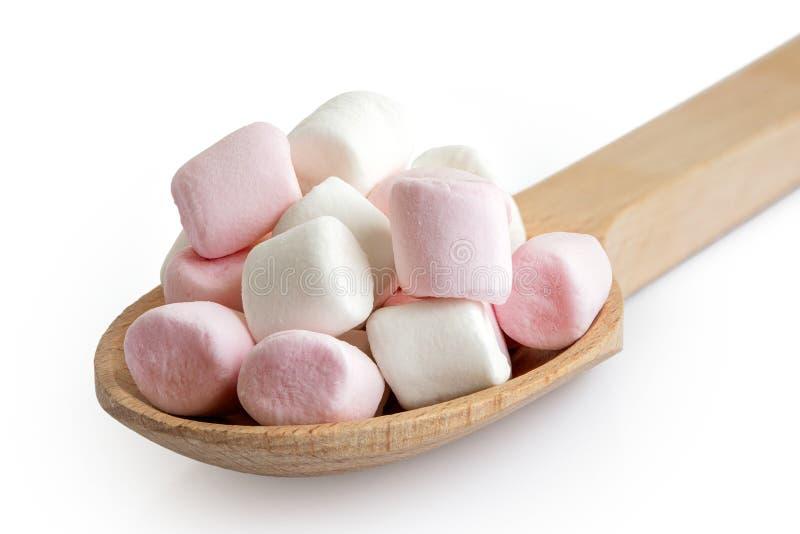 Stos menchii i białych mini marshmallows na drewnianej łyżce odizolowywającej na bielu obraz stock