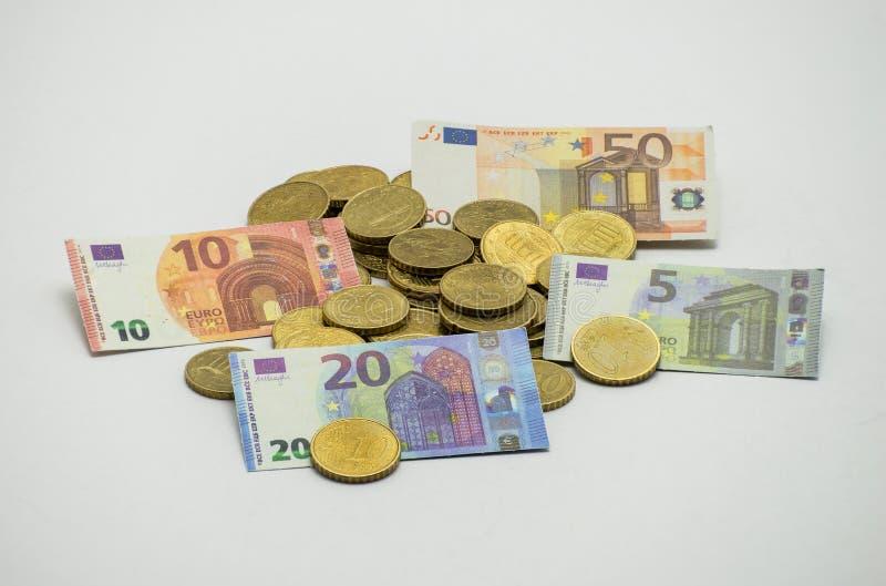 Stos monety Europejski waluta euro z miniaturowymi banknotami 5, 10, 20, 50 euro Odizolowywający na białym tle z clippin zdjęcie stock