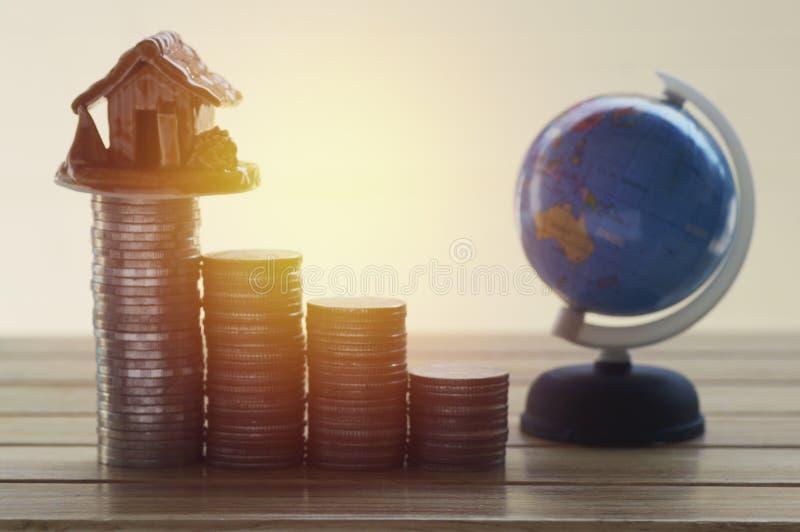 Stos monety, kula ziemska i dom, pojęcie w domu finanse obraz stock