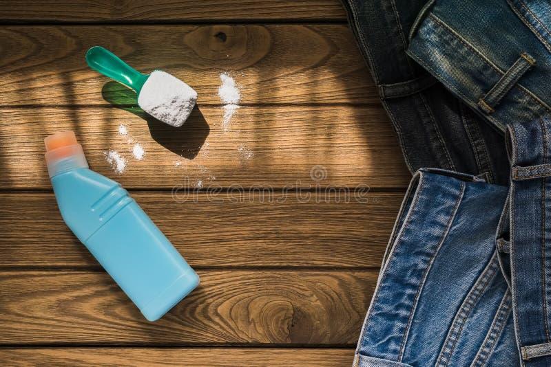 Stos niebiescy dżinsy odziewa z detergentowym i płuczkowym proszkiem dalej fotografia royalty free