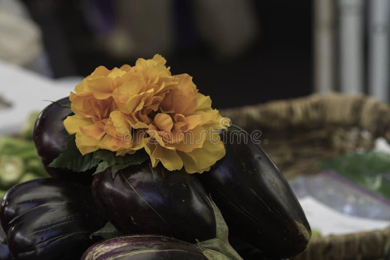 Stos oberżyna przy rynkiem dekorującym z grupą pomarańczowa tkanina kwitnie zdjęcia stock