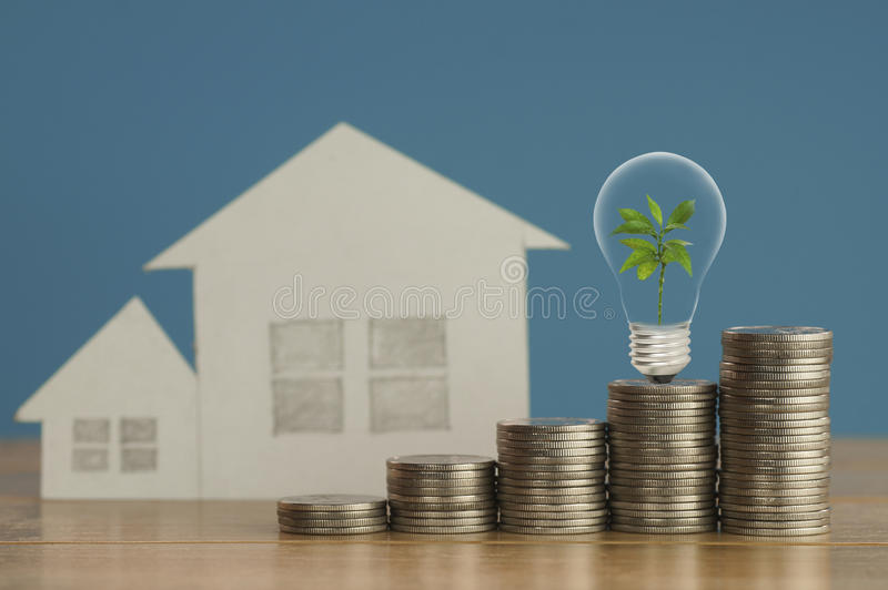 Stos pieniądze monety z małym zielonym drzewa, żarówki i papieru domem na drewnie i miękkim błękitnym tle, pojęcie w narzeczonym obrazy royalty free