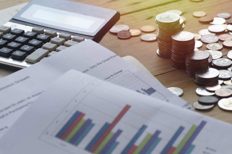 Stos pieniądze monety z wykresu kalkulatorem na drewno stole i papierem obraz royalty free