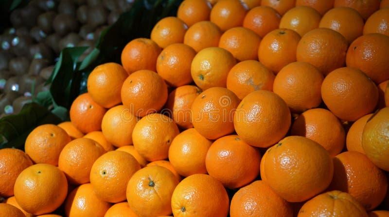 Stos pomarańcze na kontuarze w supermarkecie, zielony kiwifruit w tle zdjęcia royalty free