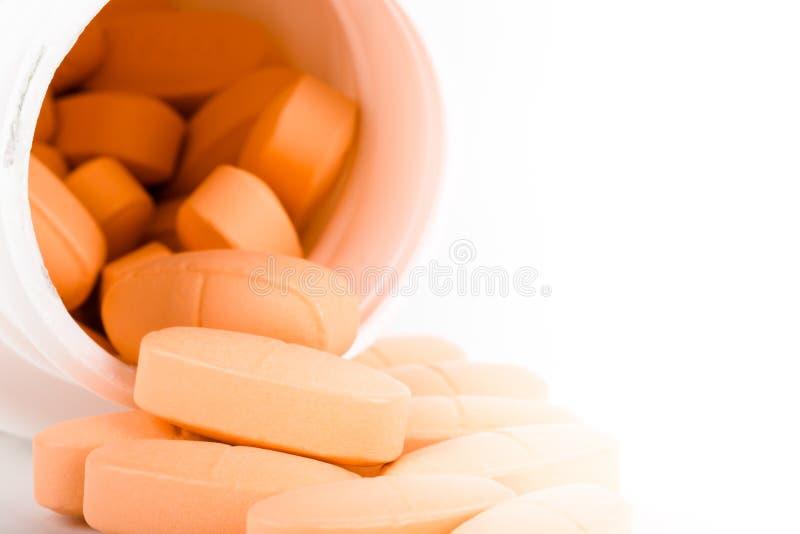 Stos pomarańczowe pigułki na lekkim tle zdjęcie stock