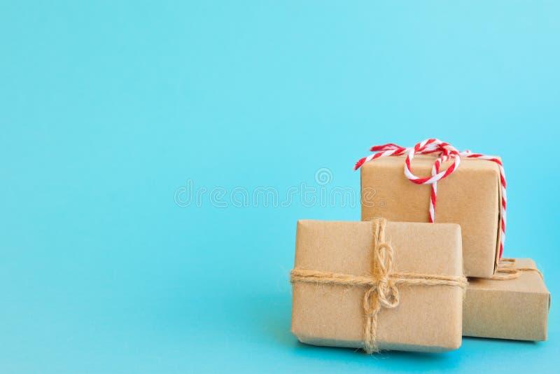Stos prezentów pudełka zawijający w rzemiosło papierze wiązał z dratwa czerwonym białym faborkiem na nowym bławym tle Nowy Rok bo fotografia stock