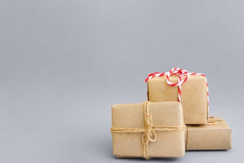 Stos prezentów pudełka zawijający w rzemiosło papierze wiązał z dratwa czerwonym białym faborkiem na popielatym Nowy Rok Bożenaro zdjęcia stock