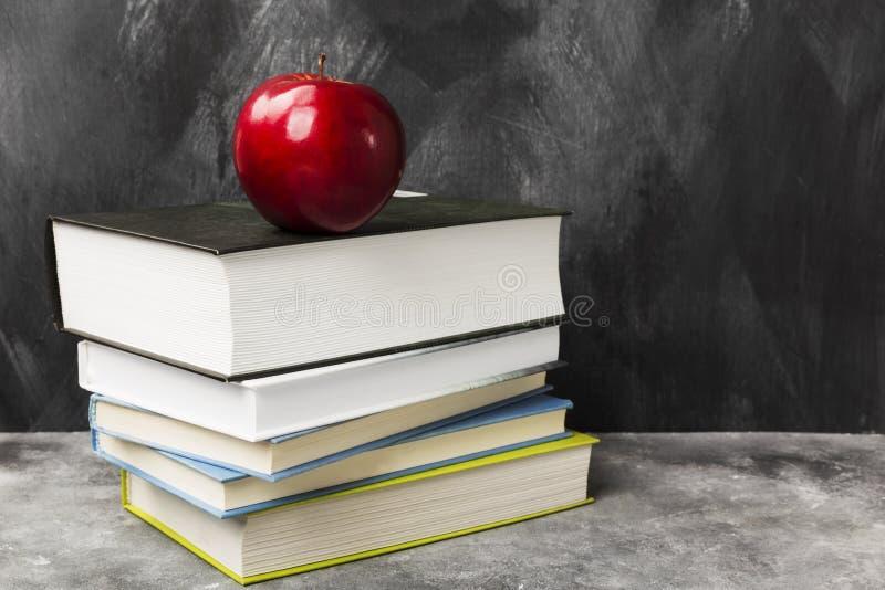 Stos różnorodne książki i czerwony jabłko na ciemnym tle Odbitkowy zdrój zdjęcie royalty free