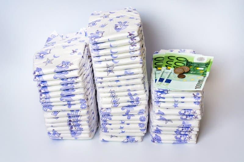 Stos rozporządzalne pieluszki z euro pieniądze zdjęcia stock
