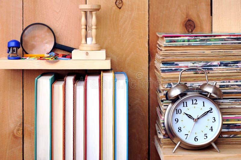 Stos stary magazyn, zegar, książki i materiały, zdjęcie royalty free