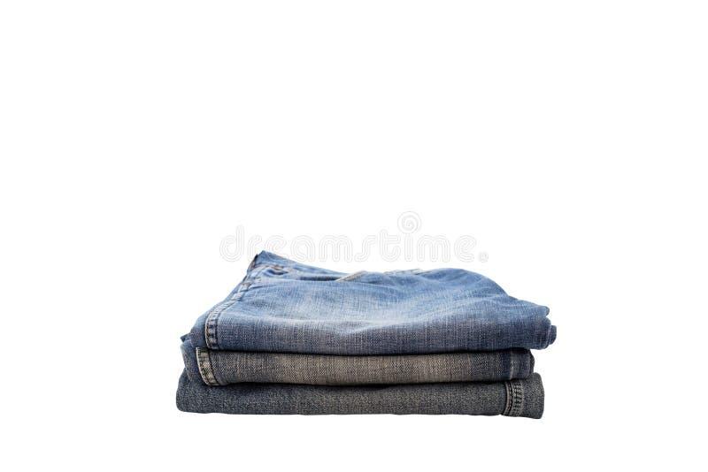 Stos ubrania, sterta niebiescy dżinsy odizolowywający na białym tle fotografia royalty free