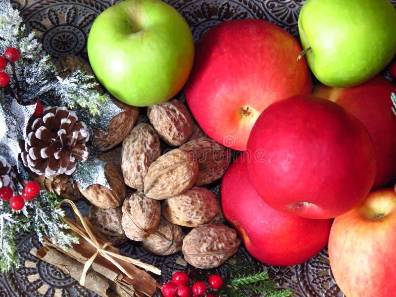 Stos widoków na grzbiet miski mosiężnej Zielone, czerwone jabłka, orzechy włoskie i masa cynamonu Fotografia w stylu ruskim zdjęcia stock