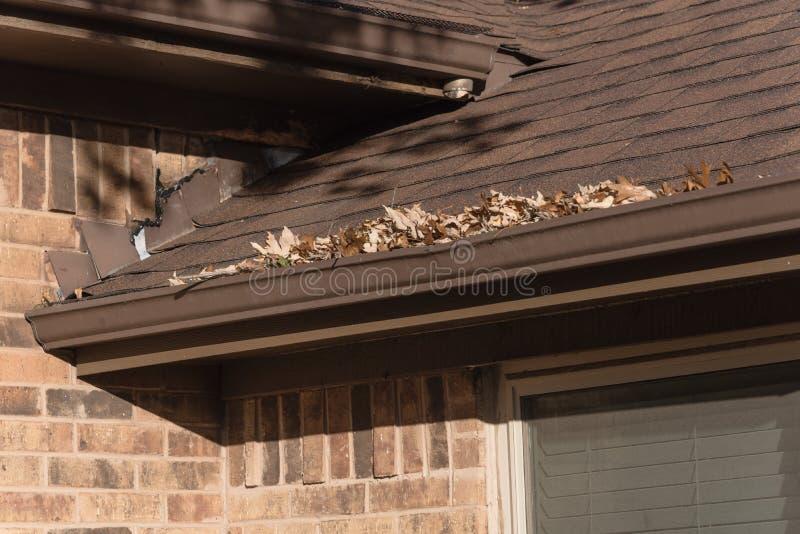 Stos wysuszeni liście na podeszczowej rynnie mieszkaniowy dom w Teksas fotografia stock