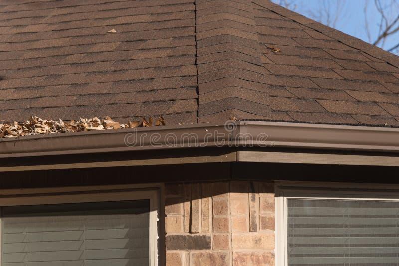 Stos wysuszeni liście na podeszczowej rynnie mieszkaniowy dom w Teksas zdjęcia stock