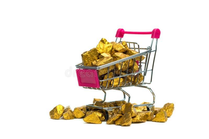 Stos złociste bryłki lub złocista kruszec w wózku na zakupy lub supermarketa tramwaju na białym tle, cennym kamieniu lub gomółce  zdjęcie royalty free