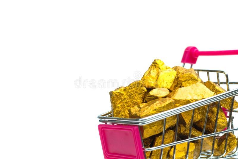 Stos złociste bryłki lub złocista kruszec w wózku na zakupy lub supermarketa tramwaju na białym tle, cennym kamieniu lub gomółce  fotografia stock