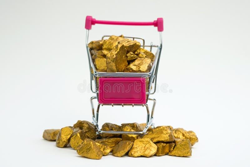 Stos złociste bryłki lub złocista kruszec w wózku na zakupy lub supermarketa tramwaju na białym tle, cennym kamieniu lub gomółce  obraz royalty free