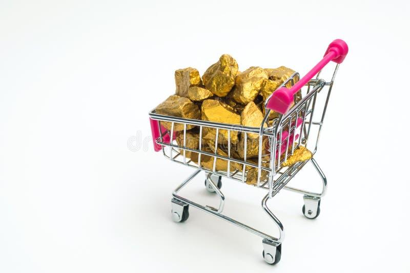 Stos złociste bryłki lub złocista kruszec w wózku na zakupy lub supermarketa tramwaju na białym tle, cennym kamieniu lub gomółce  obraz stock