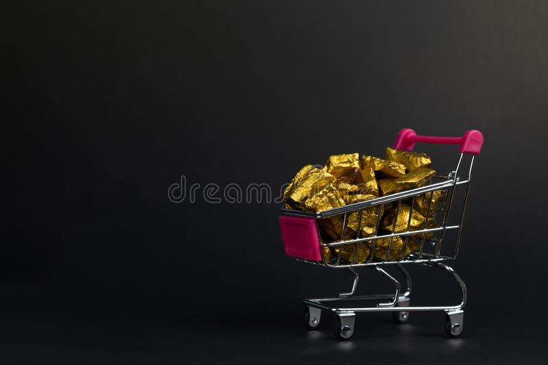 Stos złociste bryłki lub złocista kruszec w wózku na zakupy lub supermarketa tramwaju na czarnym tle, cennym kamieniu lub gomółce zdjęcia stock