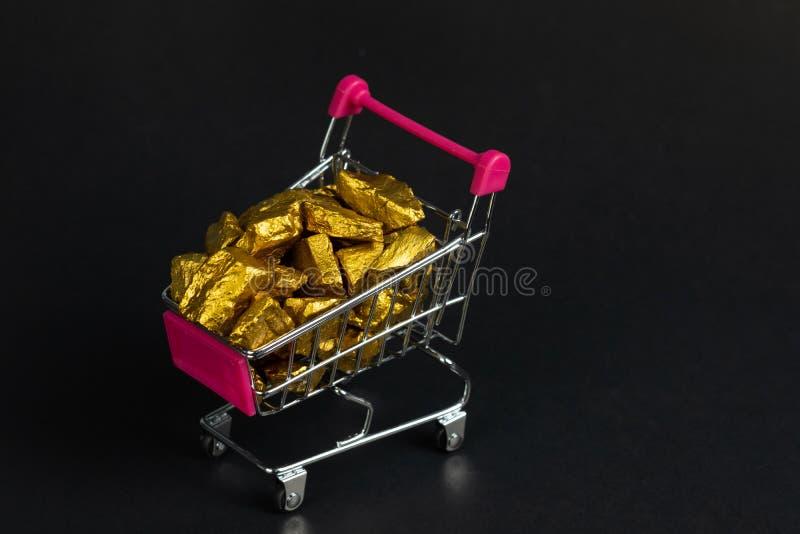 Stos złociste bryłki lub złocista kruszec w wózku na zakupy lub supermarketa tramwaju na czarnym tle, cennym kamieniu lub gomółce obrazy royalty free
