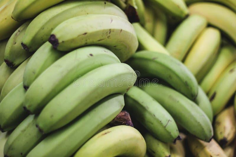 Stos zieleni banany na rolnikach wprowadzać na rynek lub robi zakupy fotografia royalty free
