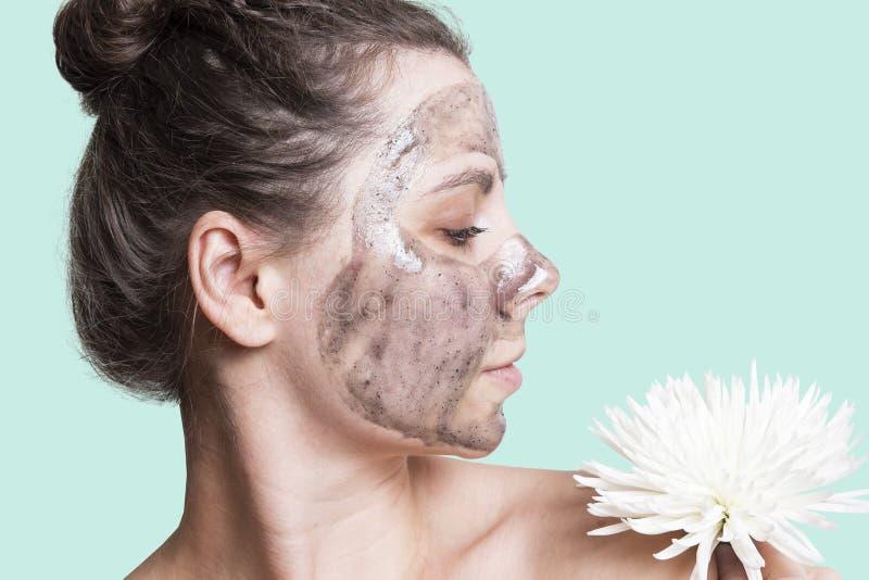 stosowanie opieki skóry przejrzystego lakier Kobieta z czarną twarzową maską i białym kwiatem zdjęcia stock
