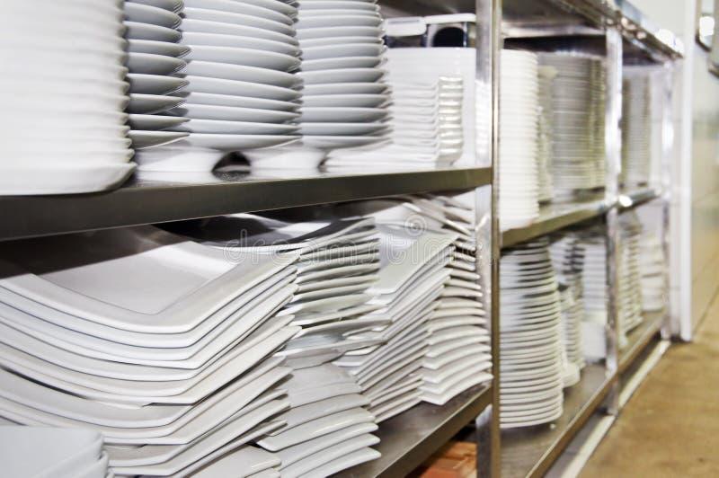 Stosy biali naczynia w restauraci i talerze obrazy royalty free