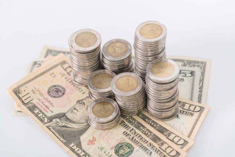 Stosy monety i dolarowa waluta na białym tle zdjęcie royalty free