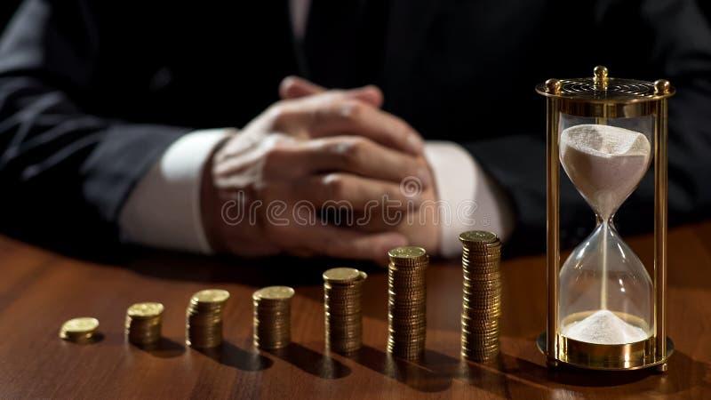Stosy monety przyrost, piaska spływanie w hourglass, biznesmena czekanie dla zysku zdjęcie stock
