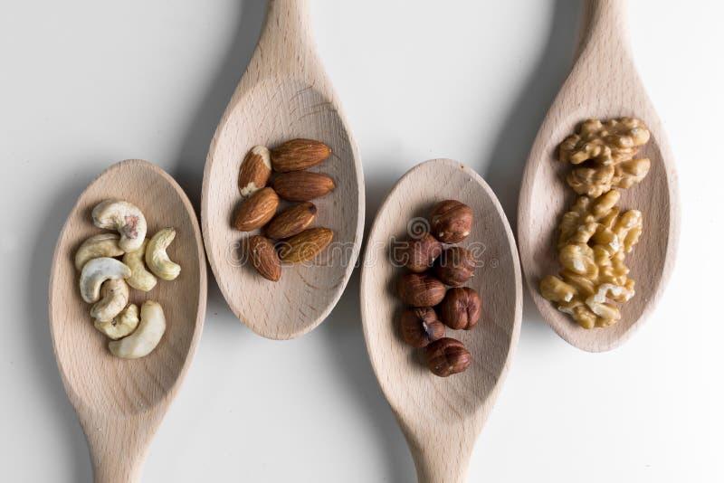 Stosy orzechy włoscy, ceshews, migdał i hazelnuts w drewnianych spoones na białym tle, Dokrętki dla zdrowie Selekcyjna ostrość zdjęcie royalty free
