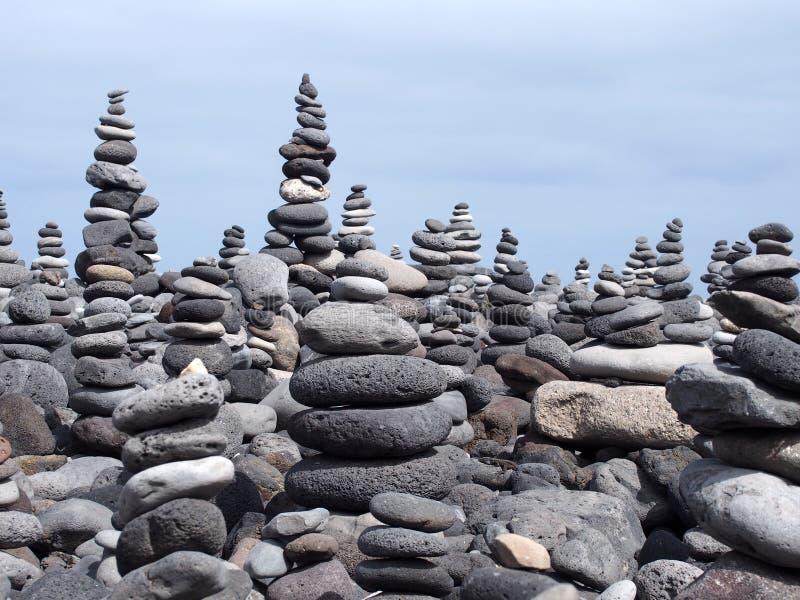 Stosy wysocy brogujący popielaci otoczaki na plaży obraz stock