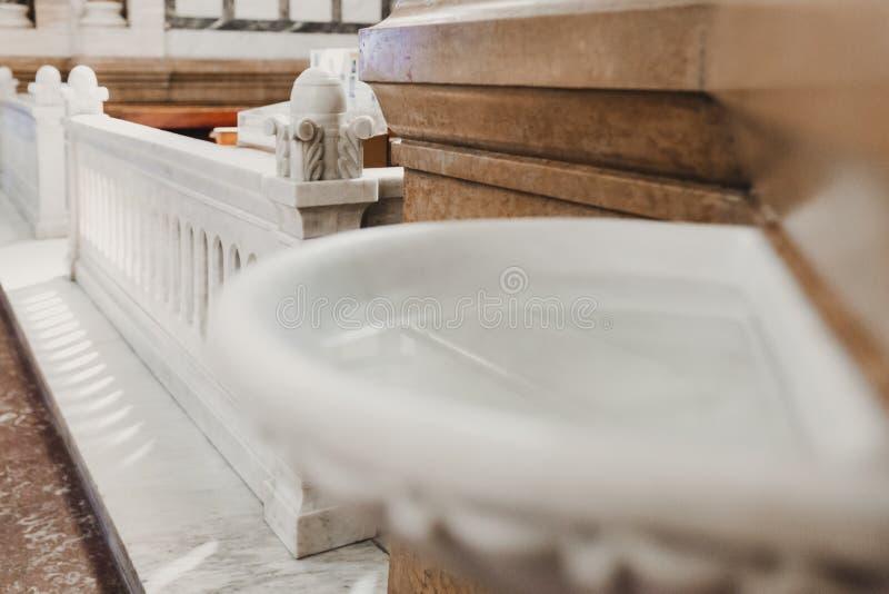Stoup святой воды, кафельный пол и стена в церков Солнечный свет фильтрованный через витраж Церковь и стоковое изображение