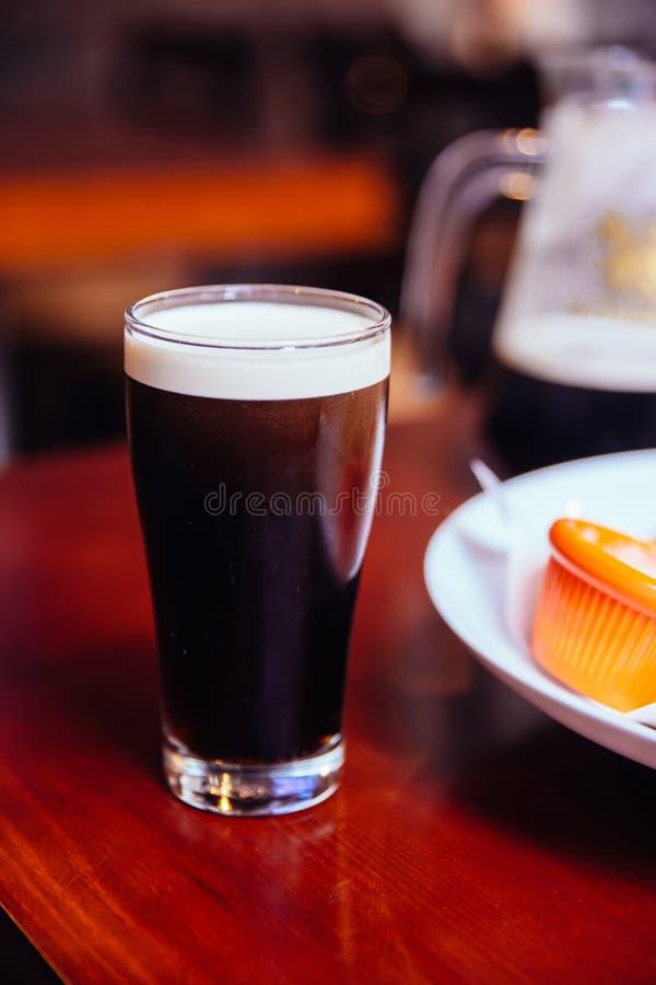 Stout schwarzes Bier im Glas auf Holztisch in der Bar stockfotos