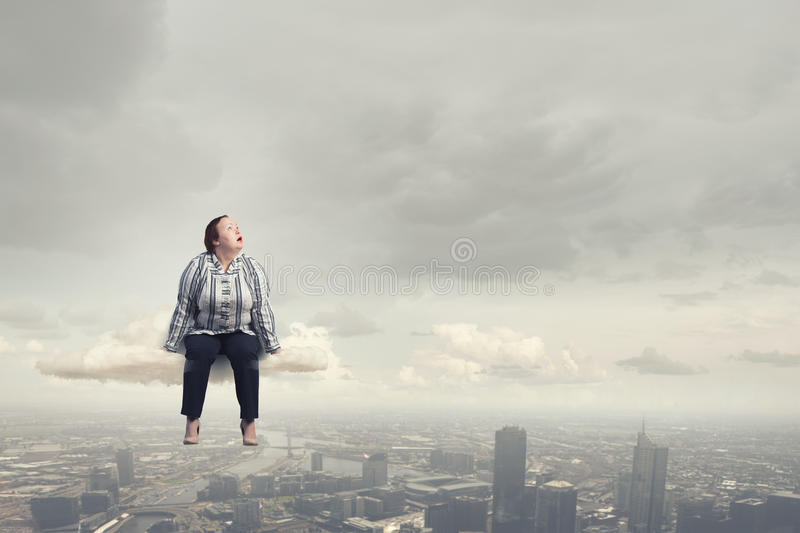 Stout woman. Concept image. Plus size woman in casual sitting on cloud royalty free stock image