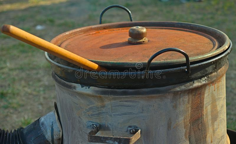 Stove made out of barrel and large covered pot with wooden spoon peaking from it royalty free stock photography